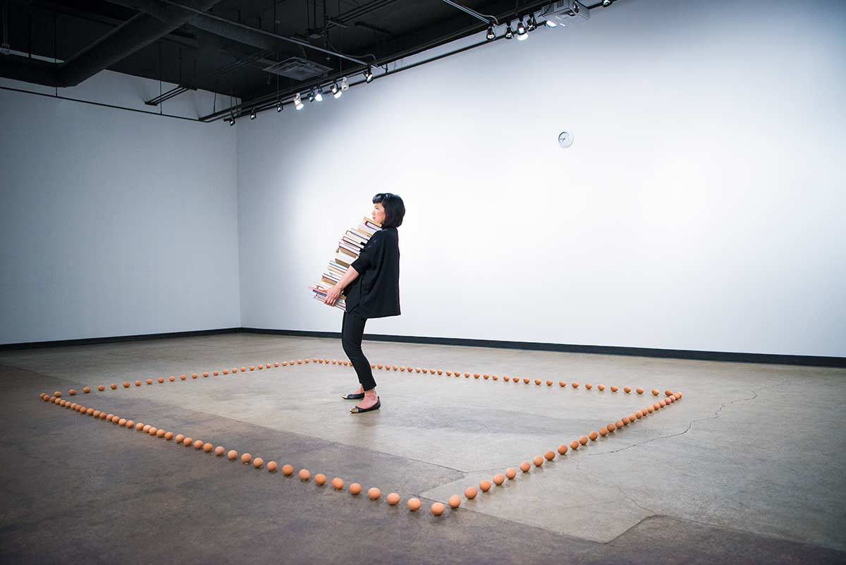 Chun Hua Catherine Dong stands in the centre of a rectangle that is made by eggs, holding a stack of books