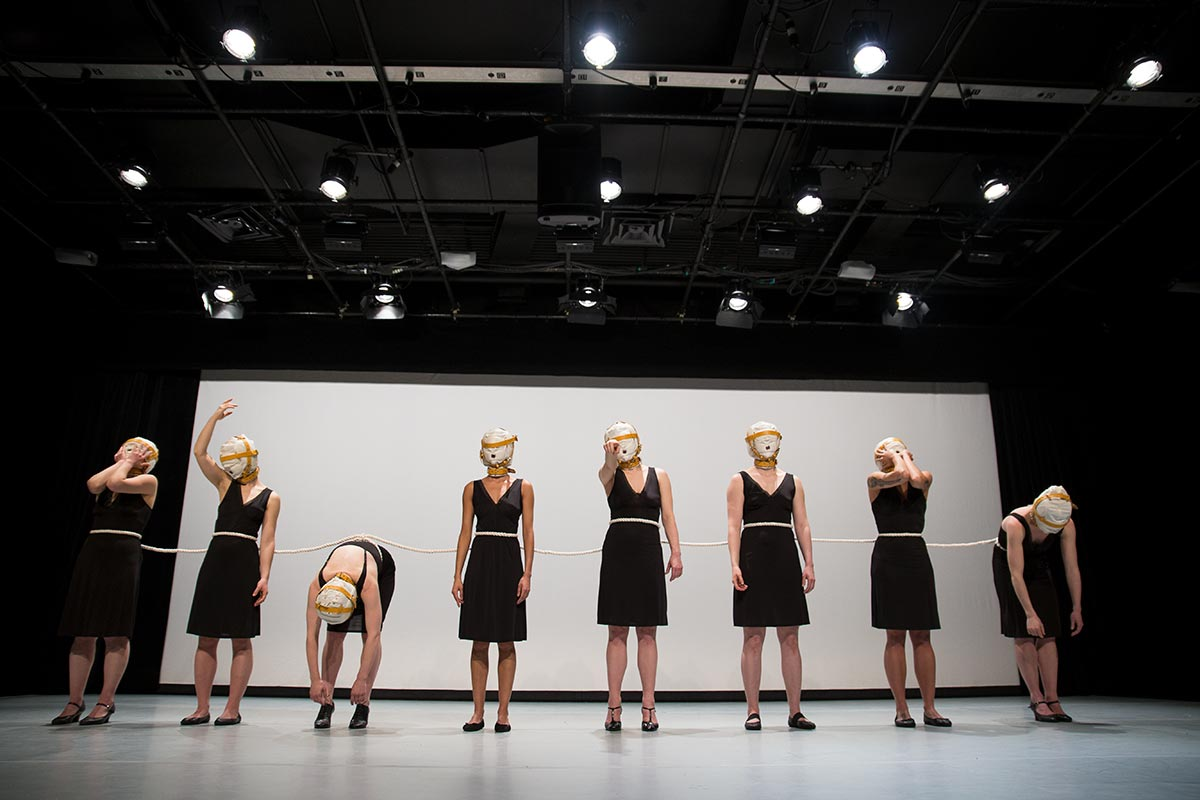 Chun Hua Catherine Dong ties eight dancers together with a rope, the dancers wear masks, standing in a row and repeating some symbolic gestures in relations to shame and vulnerability.