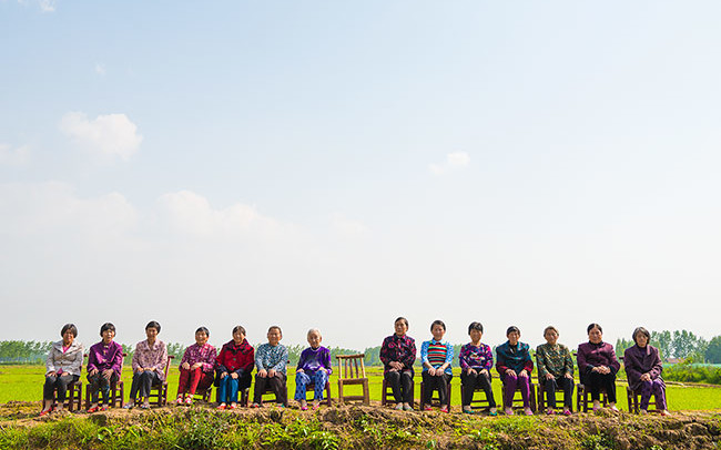 Chun Hua Catherine Dong photographs 14 mothers sitting on chairs in a countryside, an empty chair represents her lost mother