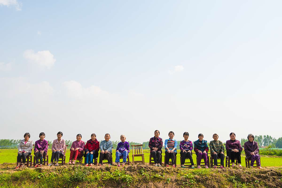 Chun Hua Catherine Dong photographs 14 mothers sitting on chairs in a countryside, an empty chair represents her mother