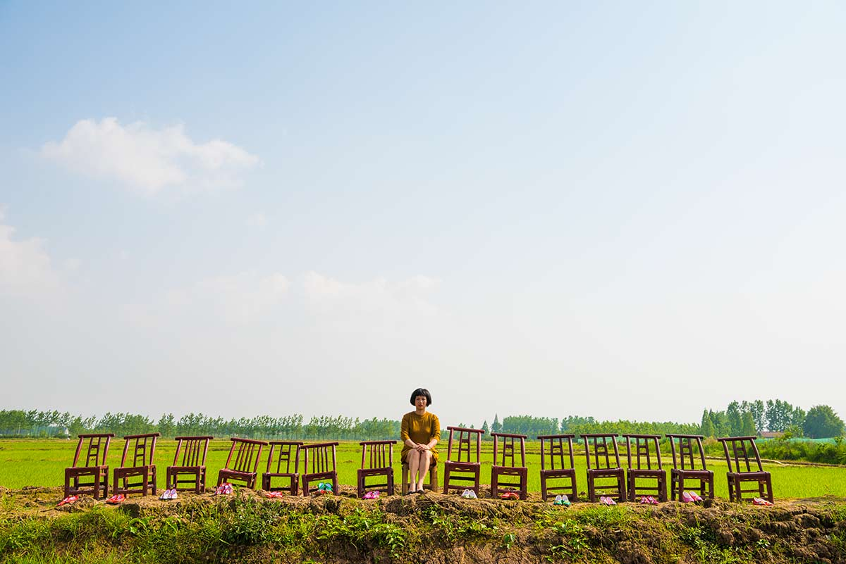 Chun Hua Catherine Dong sits on a chair with 14 empty chairs beside her in a countryside, there are 14 pairs of beautiful shows in front of chairs
