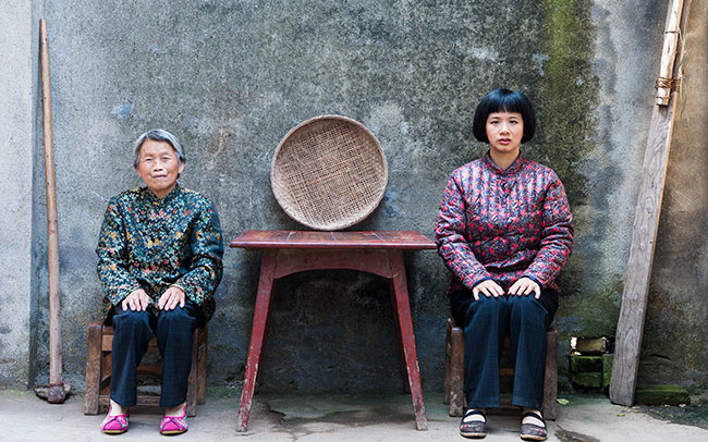 Chun Hua Catherine Dong and a mother sit beside a table, their postures mirror each other