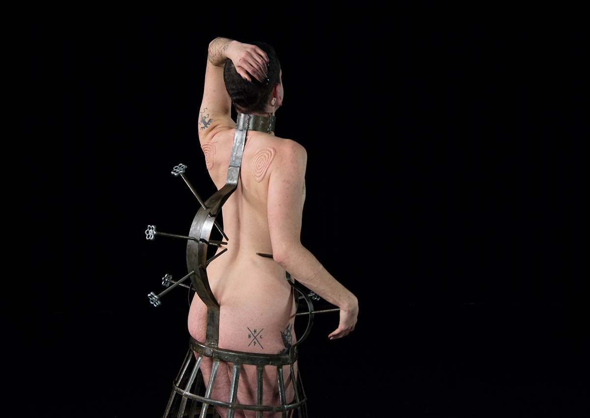 an actor locks their body in a metal corset, they dance around in a black box
