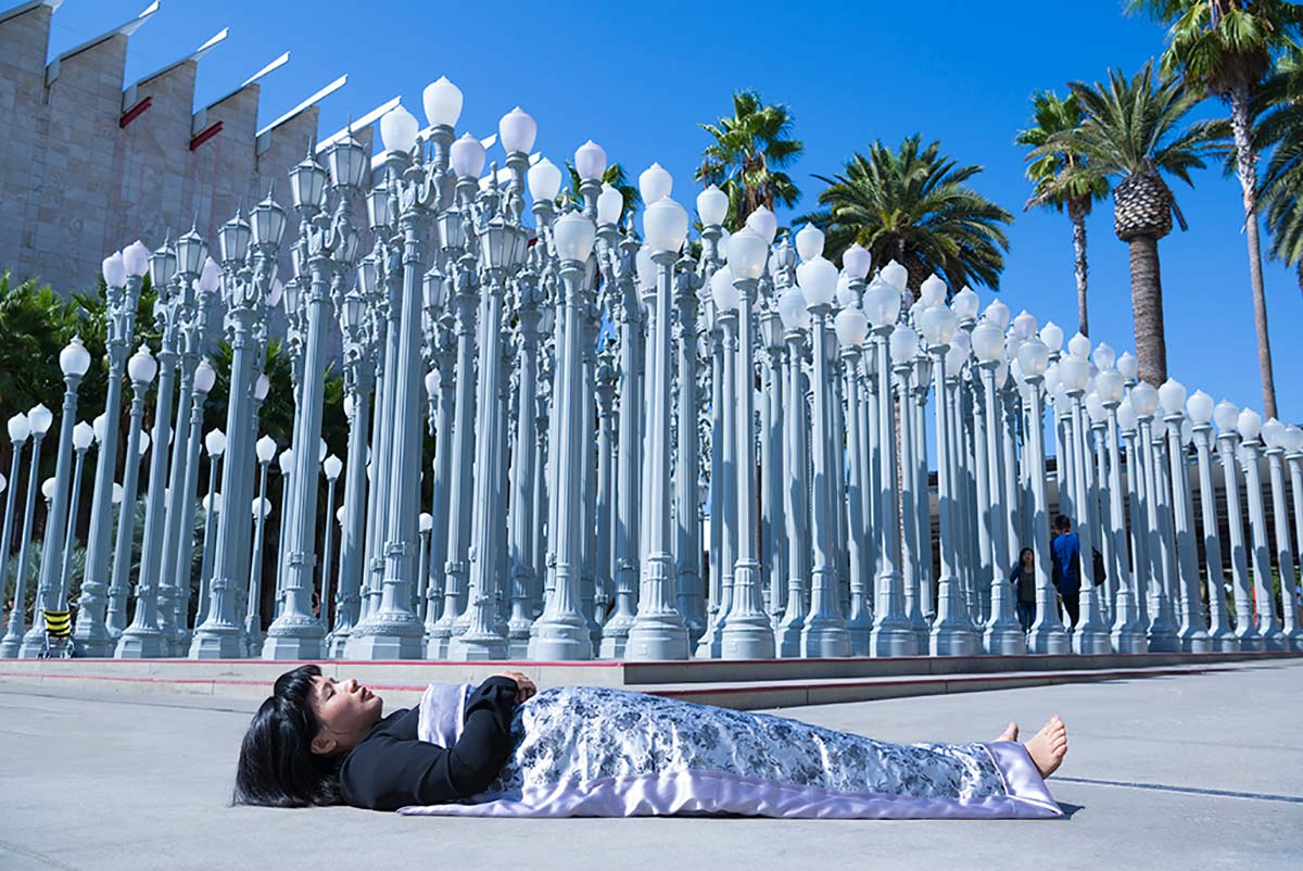 Chun Hua Catherine Dong is lying in front of famous iconic Urban Lights at LACMA in Los Angeles