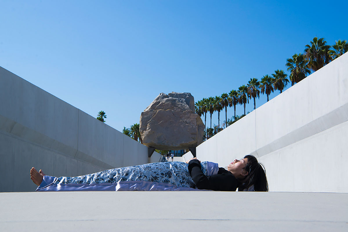 Chun Hua Catherine Dong  is lying in front of flying stone at LACMA in Los Angele