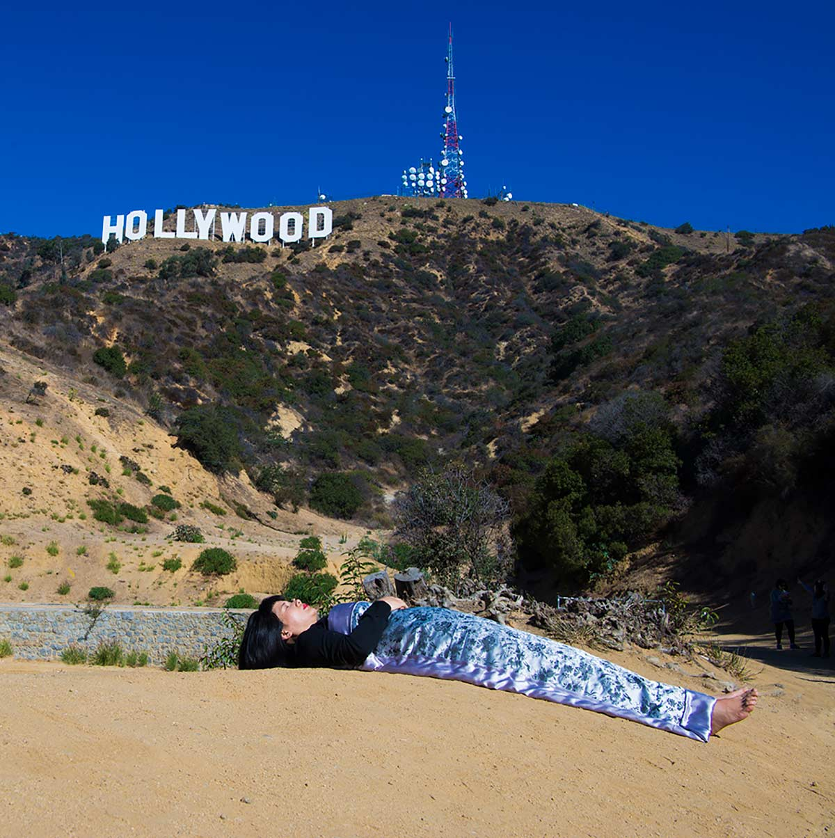 Chun Hua Catherine Dong  is lying in front of Hollywood Sign