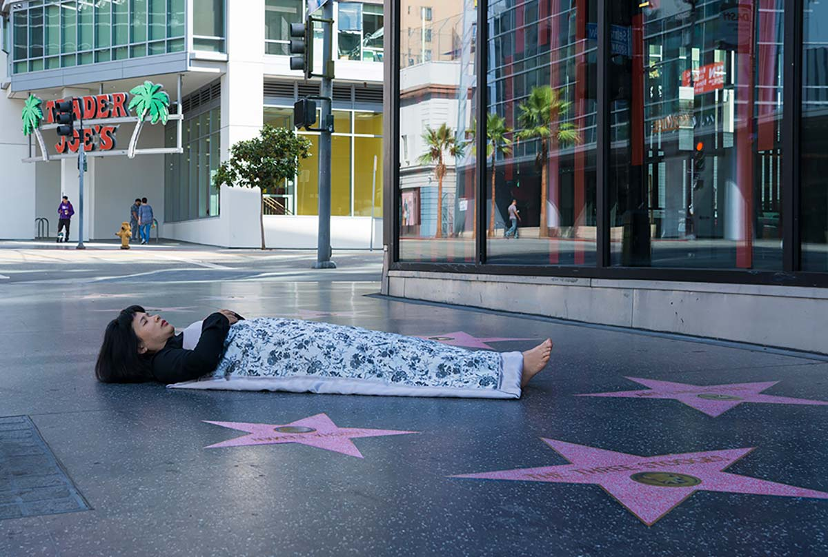 Chun Hua Catherine Dong  is lying in front of  The Hollywood Walk of Fame