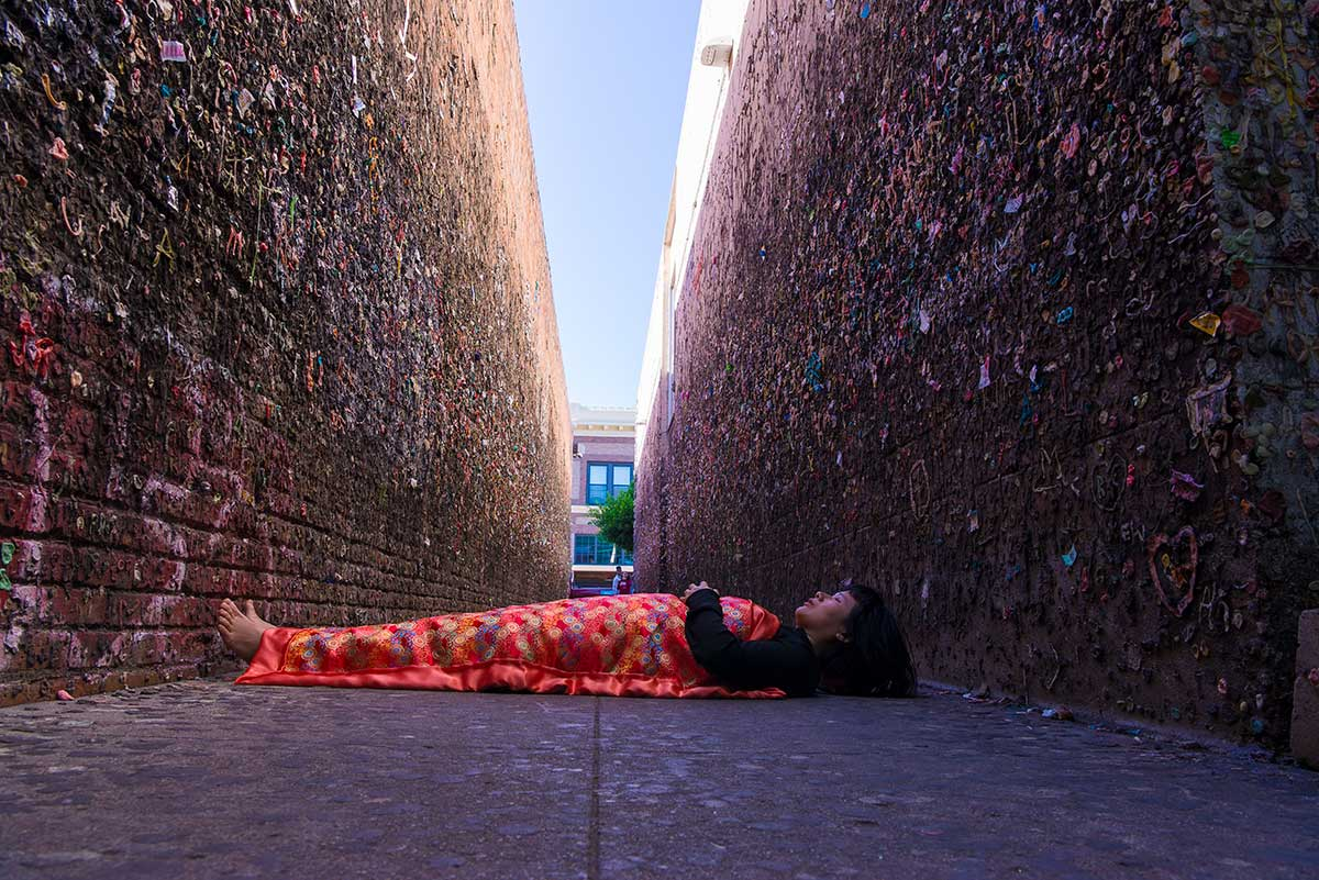Chun Hua Catherine Dong is lying in front of Bubblegum Alley in San Luis Obispo