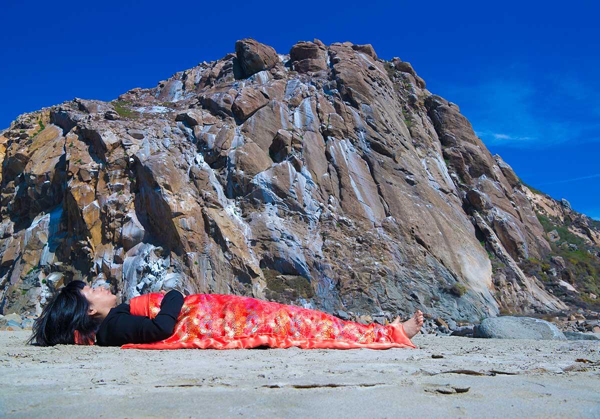 Chun Hua Catherine Dong is sleeping in front of Morro Rock in San Luis Obispo
