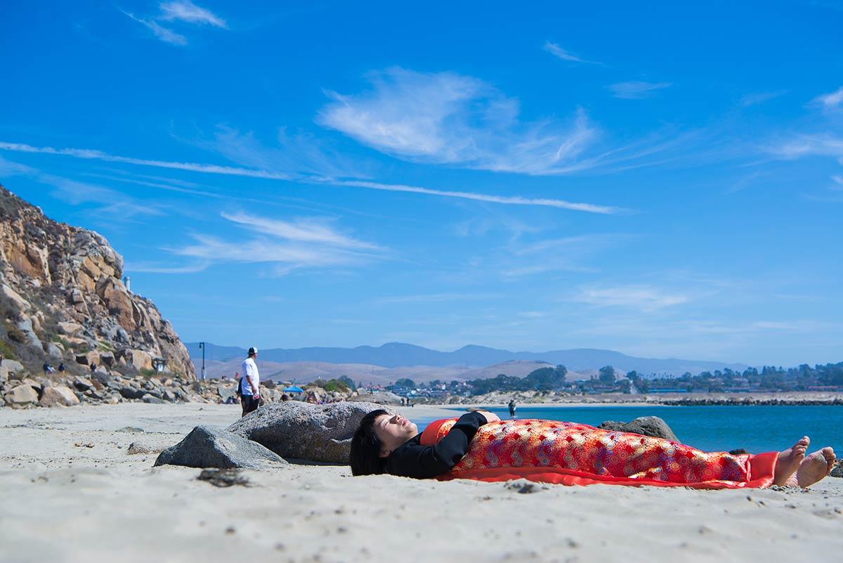 Chun Hua Catherine Dong is lying in front of Morro Bay in San Luis Obispo
