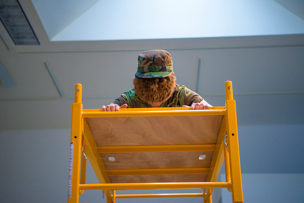 Chun Hua Catherine Dong's face is covered by a hairy mask, she wears military suit and looks down on a a scaffold