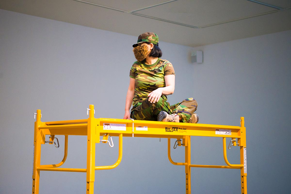 Chun Hua Catherine Dong's face is covered by a hairy mask, she wears military suit and does yoga on a a scaffold