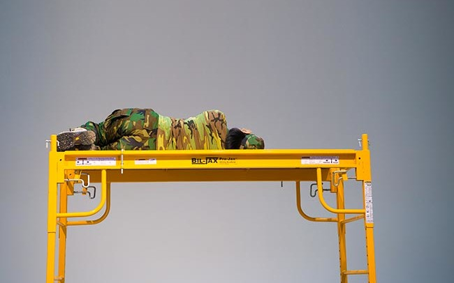 Chun Hua Catherine Dong wears military suit, lying on a scaffold