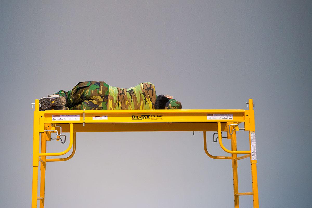 Chun Hua Catherine Dong wears military suit, lying on a scaffold