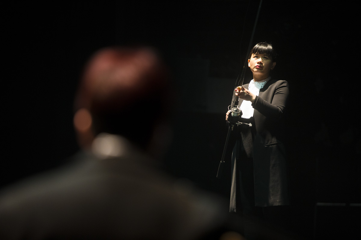 Chun Hua Catherine Dong is fishing on shredded paper while her partner gives a speech